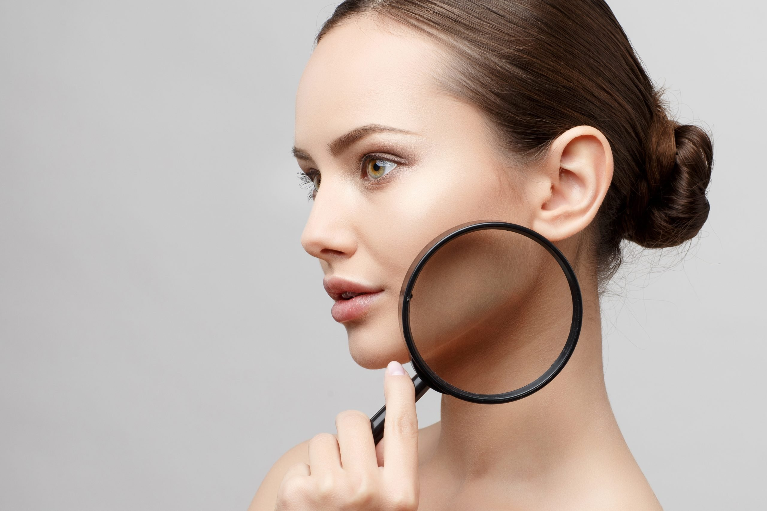Beautiful Woman with Clean Fresh Skin holding a lens